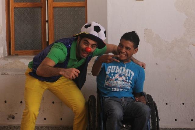 Anwar Karawi scherzt ausgelassen mit einem Jungen im Rollstuhl