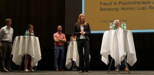 Teilnehmende und Experten diskutieren auf der Bühne.