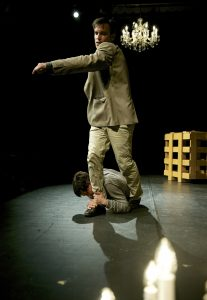 Szene auf der Bühne: Der autistische Bruder (Fabian Müller) hängt am Bein des gesunden Bruders (Silvan Kappeler).