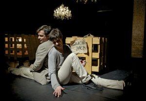 Die beiden Brüder sitzen auf der Bühne, Rücken an Rücken lehnend, in liebevollem Gespräch miteinander.