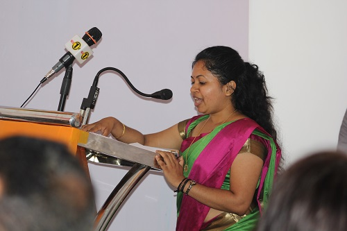 Rega Rathagirushnan steht im farbenfrohen Sari am Rednerpult