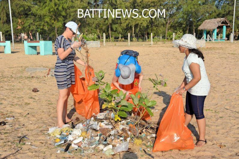 Drei Unternehmerinnen des Teams haben einen Berg Plastik und Unrat am Strand zusammengetragen und packen ihn in grosse orange Abfallsäcke.