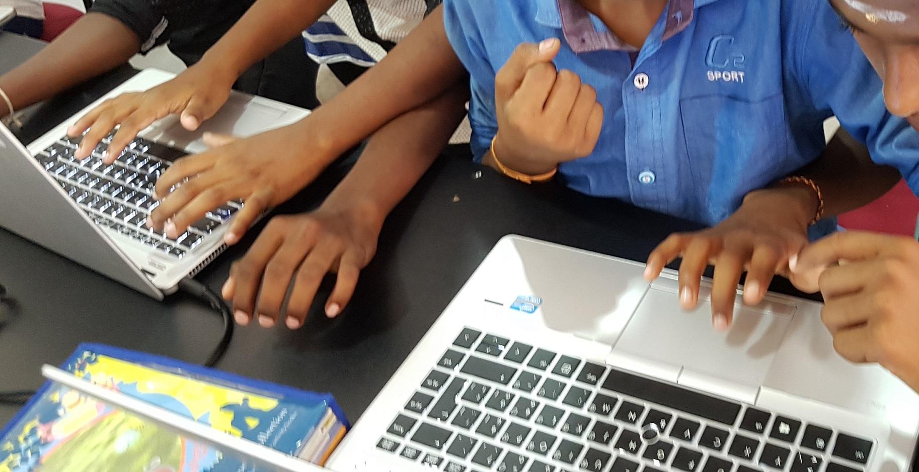 Acht Kinderhände tummeln sich an zwei Laptops
