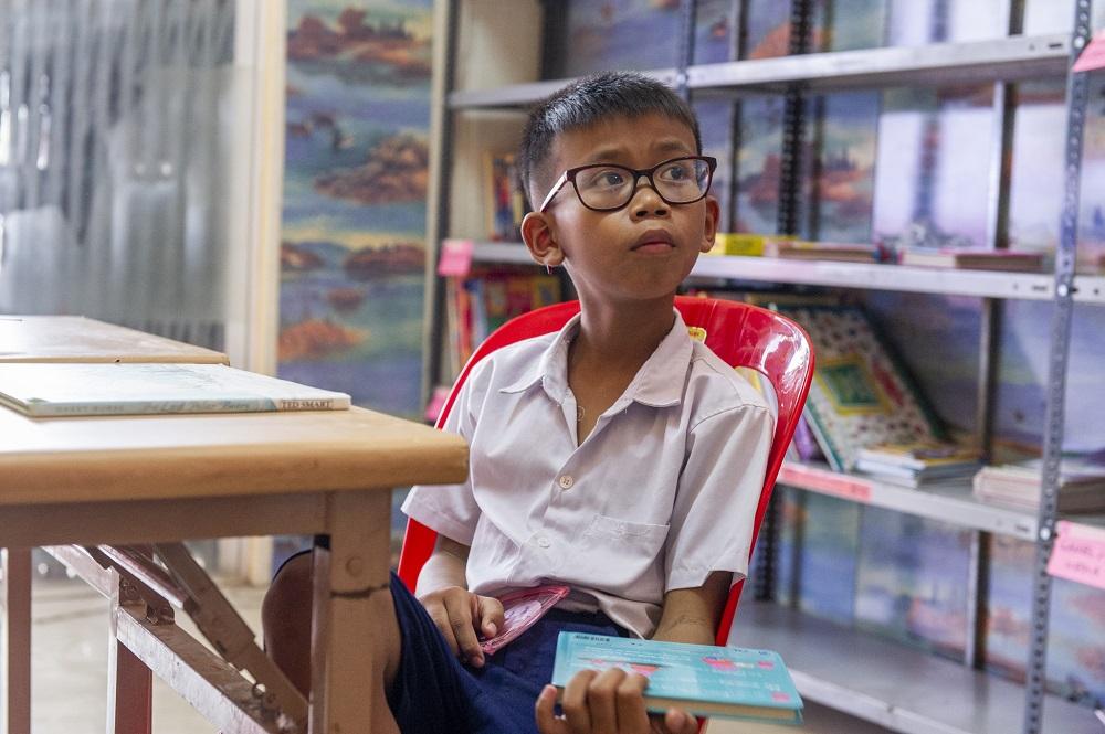 Kambodschanischer Junge mit Kinderbuch in einer Bibliothek