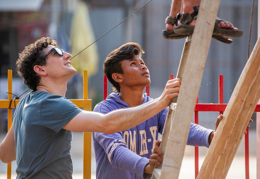Planen und anpacken. Ein Teammitglied auf der Leiter, zwei Kollegen stabilisieren die Leiter.