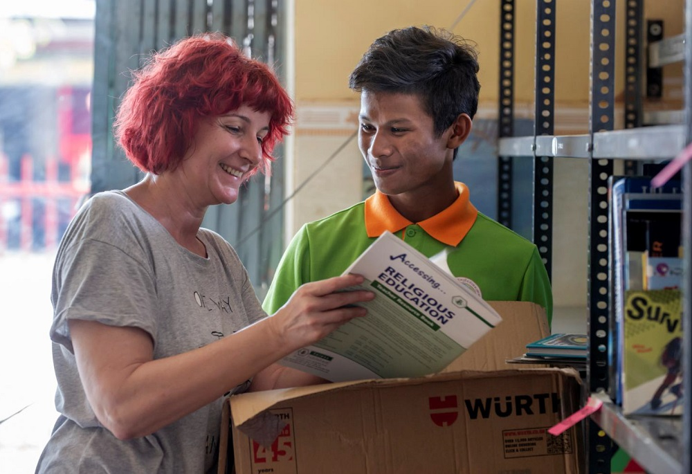 Sanha und eine Teamkollegin im Gespräch mit Recherchematerial in Händen.