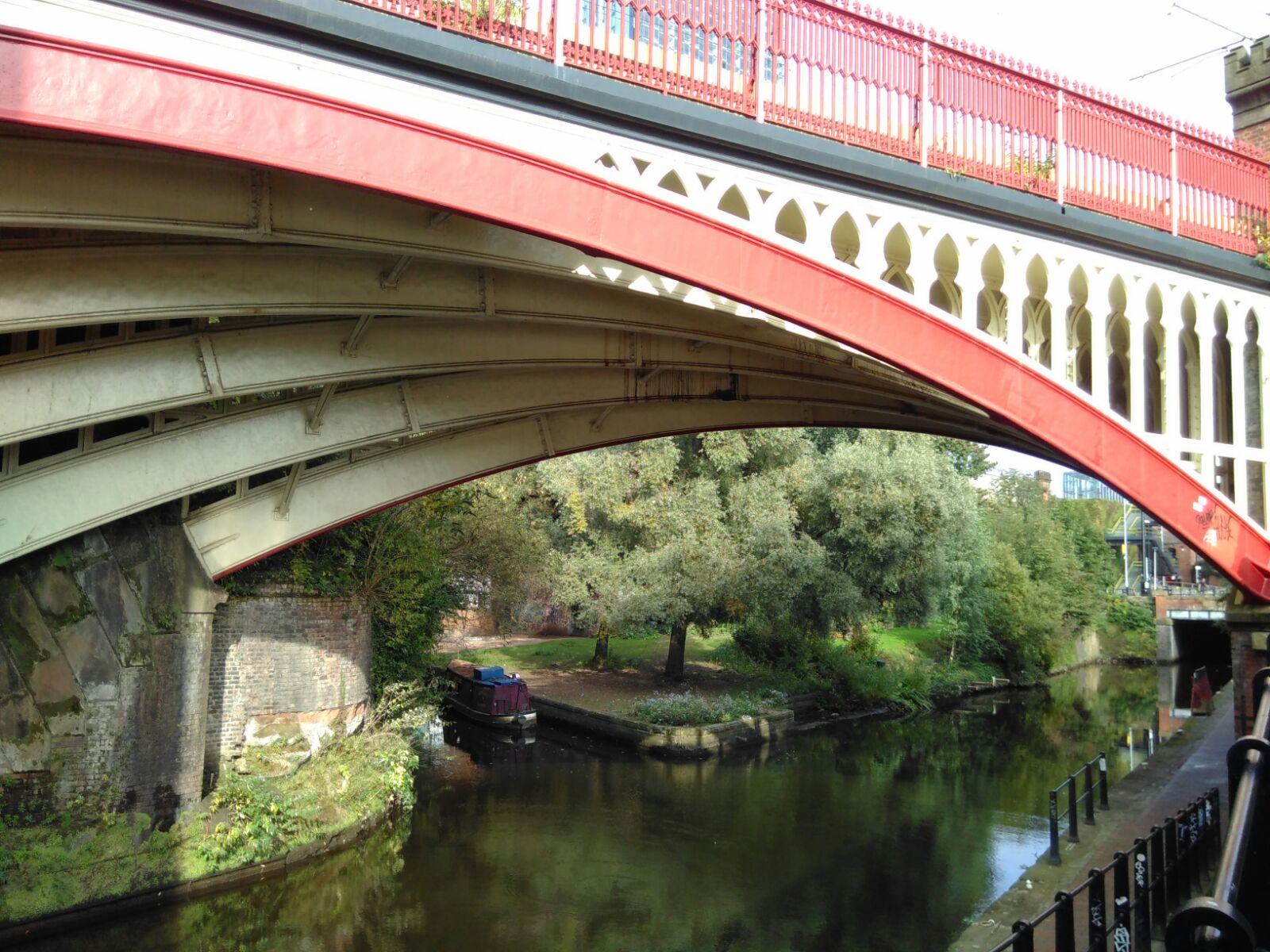 a red painted bridge over a canal