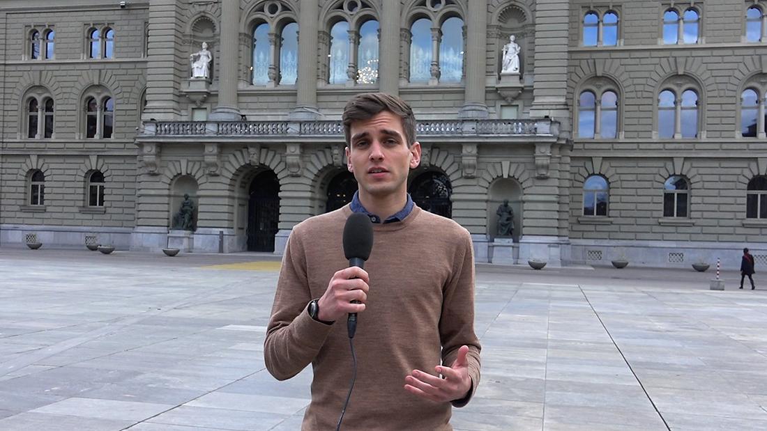 Junger Student mit Mikrophon vor dem Bundeshaus in Bern