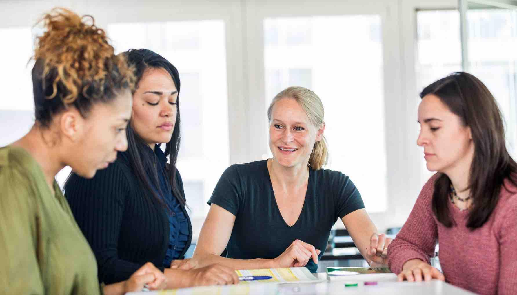 Vier Frauen sitzen an einem Tisch im Unterricht für Deutsch als Fremd- und Zweitsprache