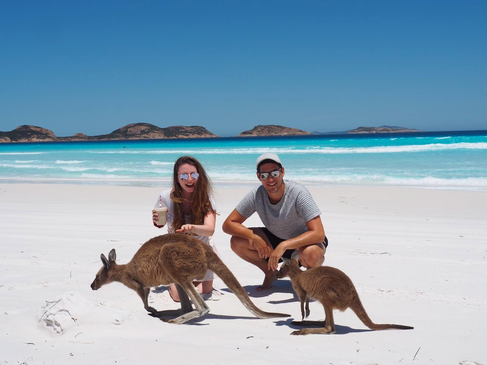 Dalia posiert mit ihrem Mann und einem Getränk in der Hand auf Kangaroo Island mit zwei Kängurus,