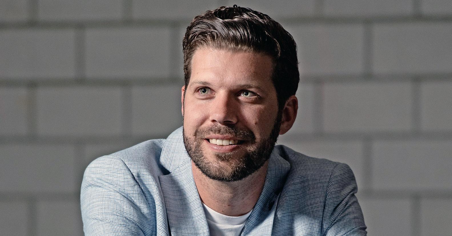 Patric Schönberg, Absolvent des CAS Digitale Transformation, sitzt vor einer Steinmauer