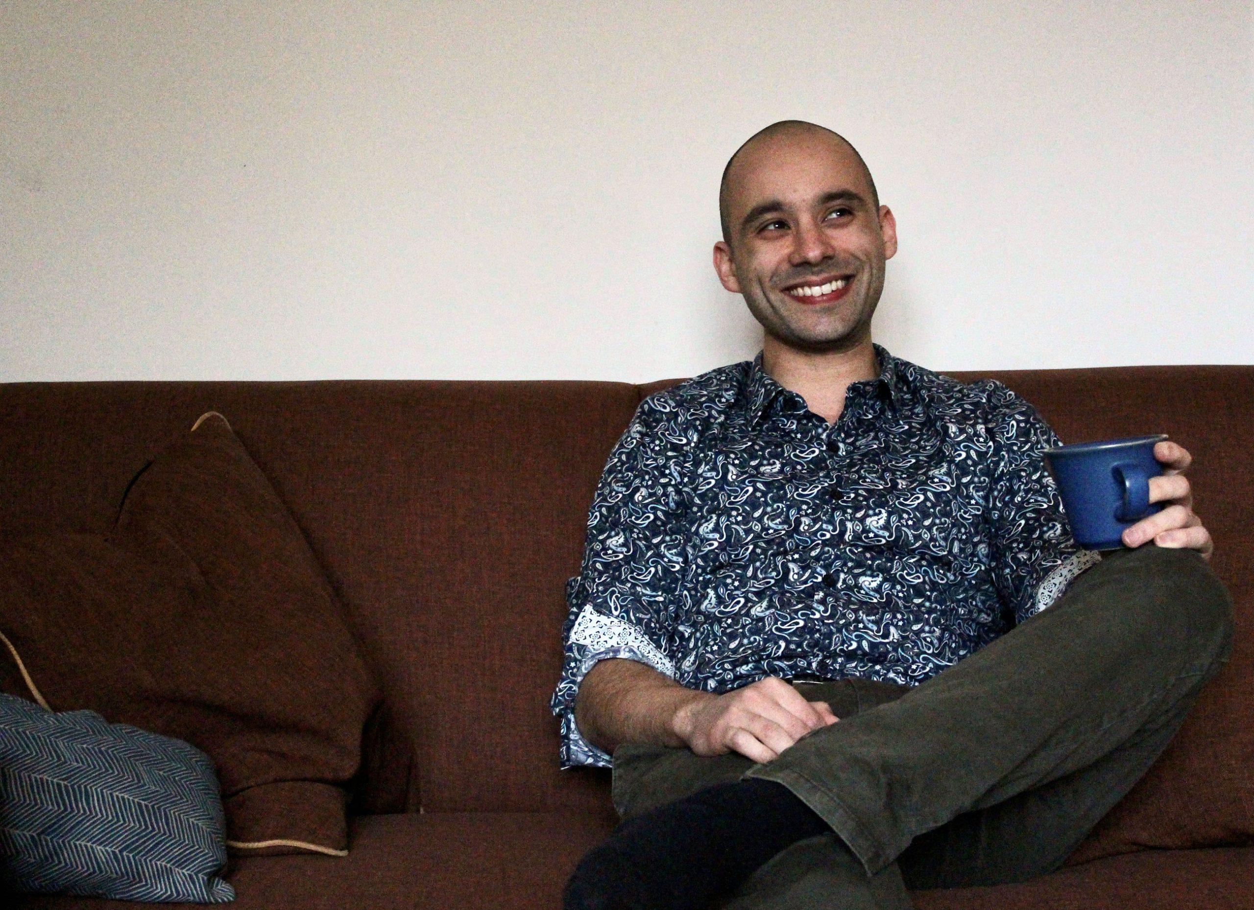 Joshua Bartholdi ist wissenschaftlicher Assistent am ILC. Hier sitzt er auf einem Sofa und trinkt Kaffee.