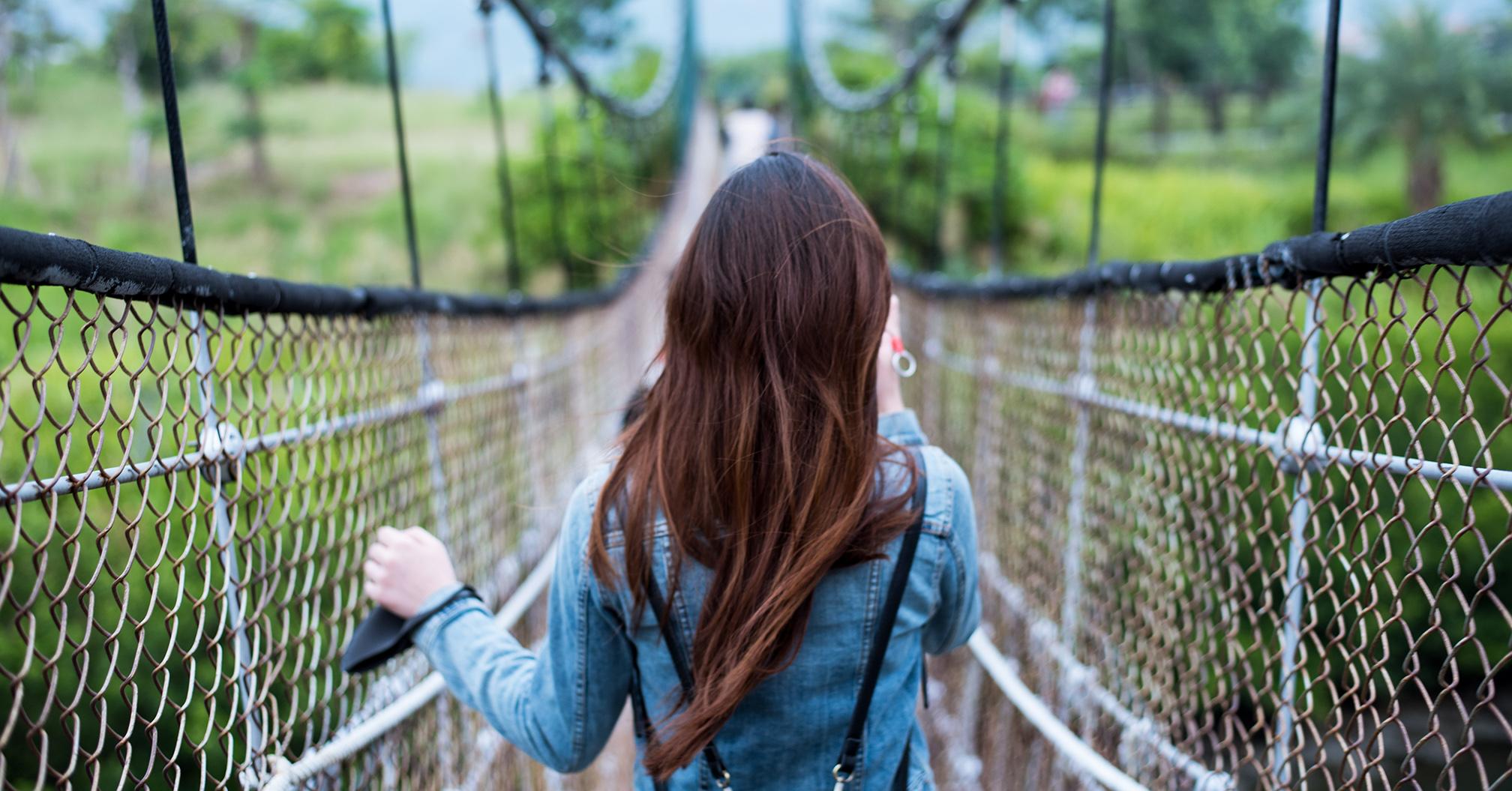 Junge Frau auf einer Luftbrücke zum Thema Leichte Sprache in barrierefreier Kommunikation.