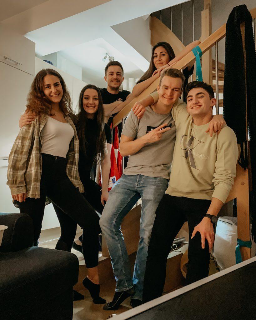 Sechs Student:innen im Wohnheim. Gruppenfoto vor einer Treppe.
