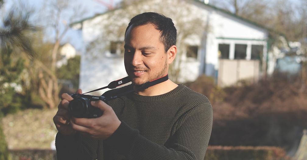 Student mit Fotokamera in der Hand im Garten stehend.