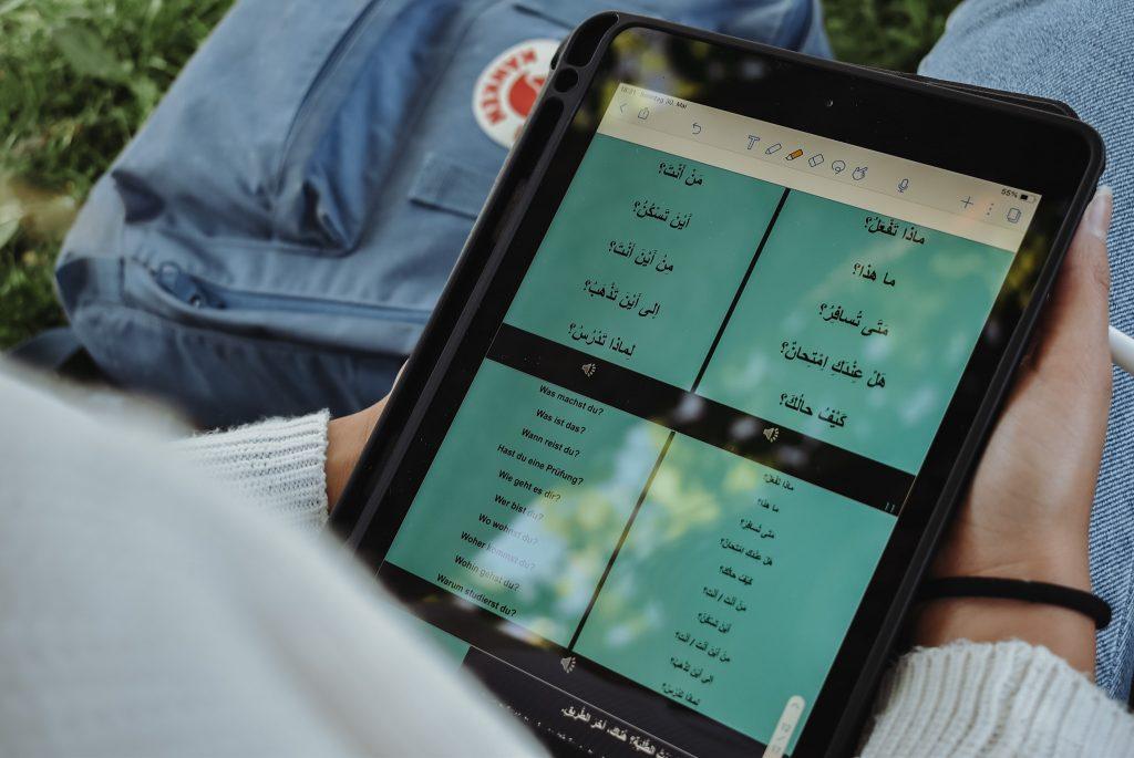 Studentin lernt Arabisch auf dem Tablet mit Tandem-Partner