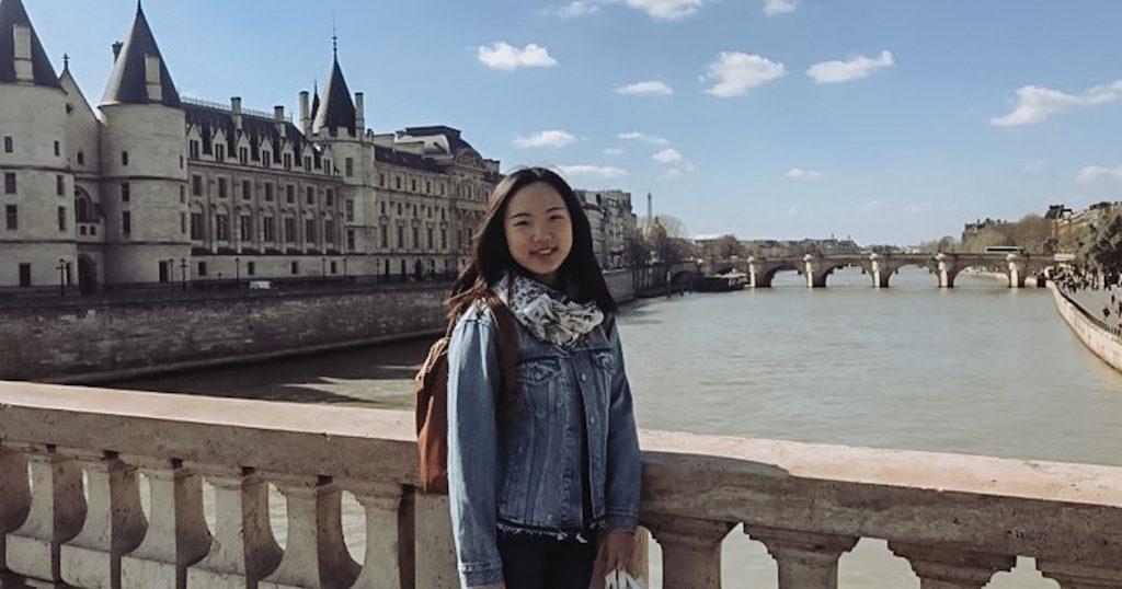Hasel Chin, Gaststudentin aus China, auf einer Brücke. Im Hintergrund ein Schloss vor blauem Himmel.