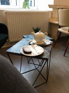 Auf einem Wohnzimmertischchen steht Kuchen und Tee bereit.