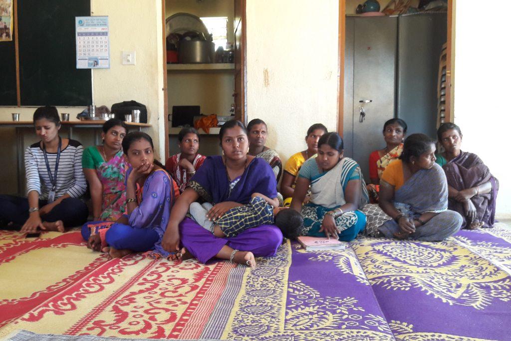 Indische Frauen einer Selbsthilfegruppen sitzen am Boden
