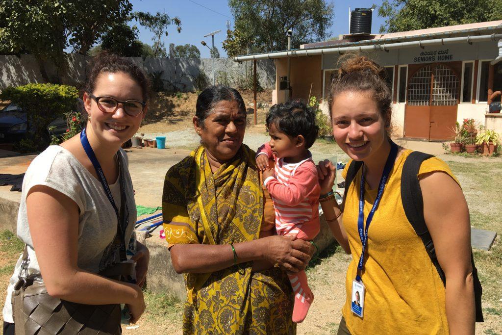 zwei Studierende der ZHAW Soziale Arbeit zusammen mit einer Dame des Aidshospiz, die die kleine Gracy auf den Armen hält.