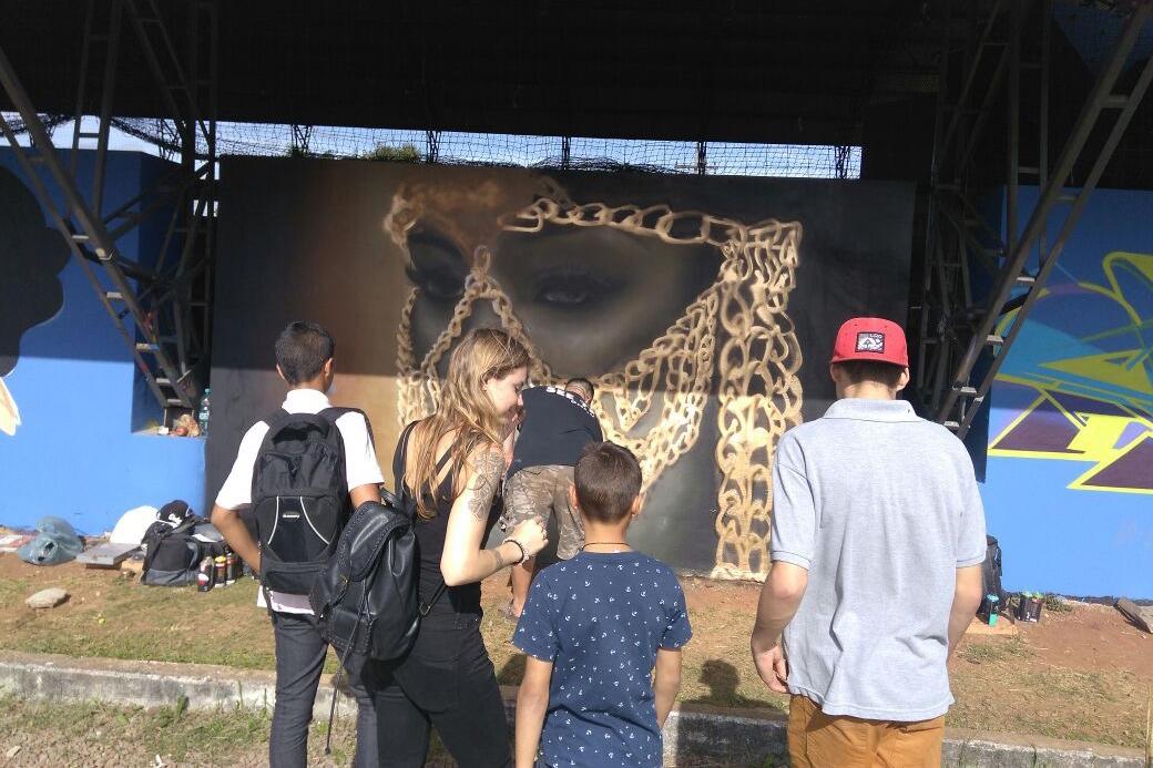 Austauschstudentin Dominique schaut mit den brasilianischen Jungen einem Graffitikünstler zu.