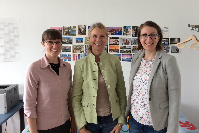 3 Frauen lächelnd vor einer Wand, die mit Ansichtskarten bestückt ist.