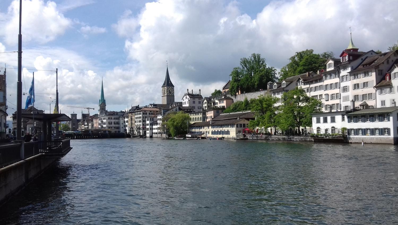 Blick auf den Fluss Limmat inmitten von Zürich. Auf der rechten Seite befindet sich die Alstadt mit Häusern und Kirchentürmen. Auf der linken Seite befindet sich die Flusspromenade Limmatquai.
