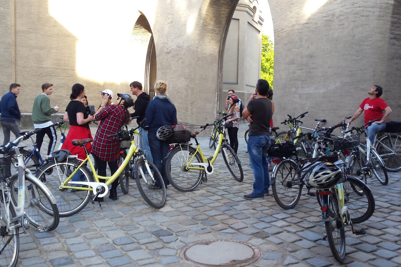 Eine Gruppe Leute stehen neben ihren Fahrrädern, auf welchen sie eine Stadtbesichtigung machen.