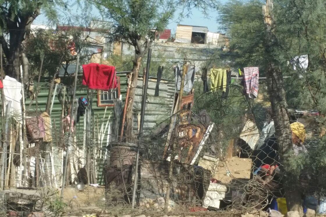 Wellblechhütte in Namibia. Vordran hängen Wäscheleinen mit Kleidungsstücken.