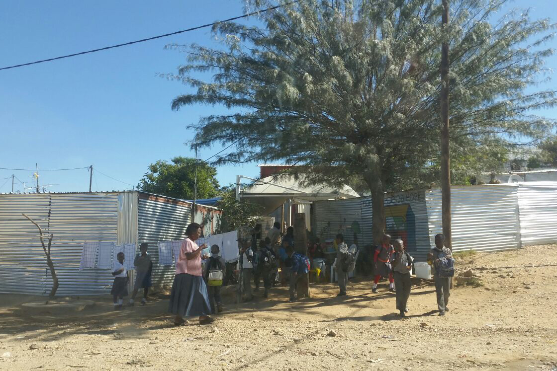 Afrikanische Kinder und Erwachsene stehen vor Wellblechhütten unter einem riesigen Baum.