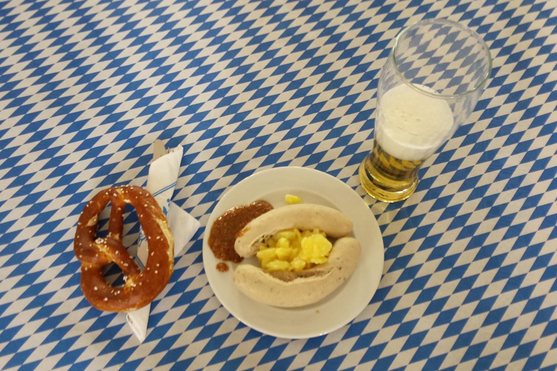 Brezel, Weisswurst und Bier auf einem blau-weiss-gemusterten Tischtuch in München.