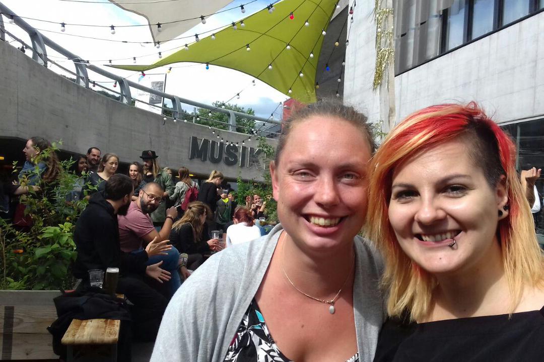 Zwei Austauschstudentinnen lächeln und stehen vor dem Musikklub Mehrspur beim Toni-Areal in Zürich.