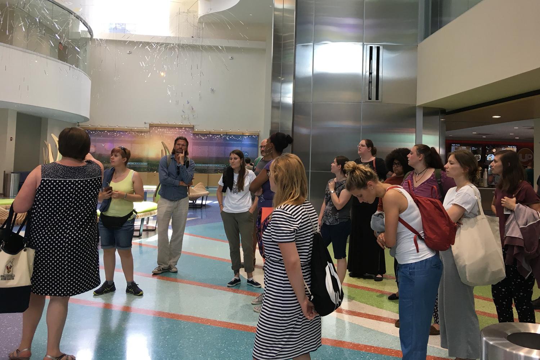 Studierende und Mitarbeitende in einem Kinderhospiz in Dayton Ohio. Sie hören aufmerksam einer Frau zu, die etwas über das Hospiz erzählt.