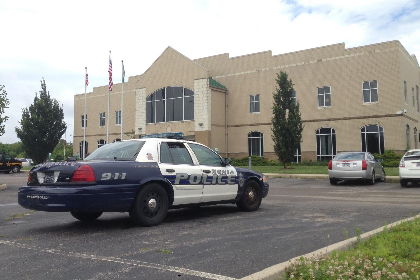 Ein blau-weisses amerikanisches Polizeiauto steht auf einem Parkplatz vor einem Gefängnis.