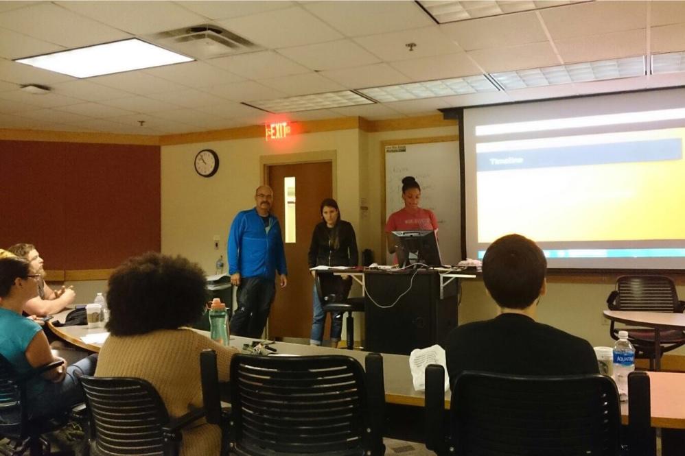 Studierende in einem Klassenzimmer während einer Präsentation. Drei Studierende stehen vorne.