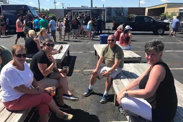 Leute sitzen auf Holzpalletten auf einem Platz und lächeln in die Kamera. Im Hintergrund sieht man Foodtrucks, vor welchen Leute stehen.
