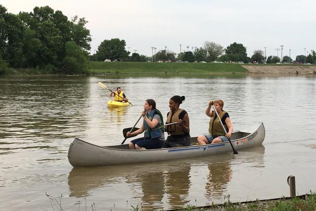 Drei junge Frauen sitzen in einem Kanu und rudern zusammen einen Fluss hinauf. Im Hintergrund sieht man einen Mann in einem gelben Kajak.
