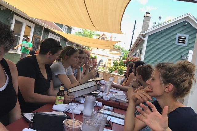 Studierende an einem langen Tisch beim Mittagessen.