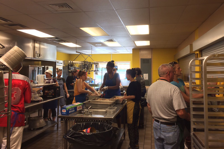Freiwillige stehen in einer Küche und bereiten Essen vor, das in einer Suppenküche für Mittellose ausgegeben wird.