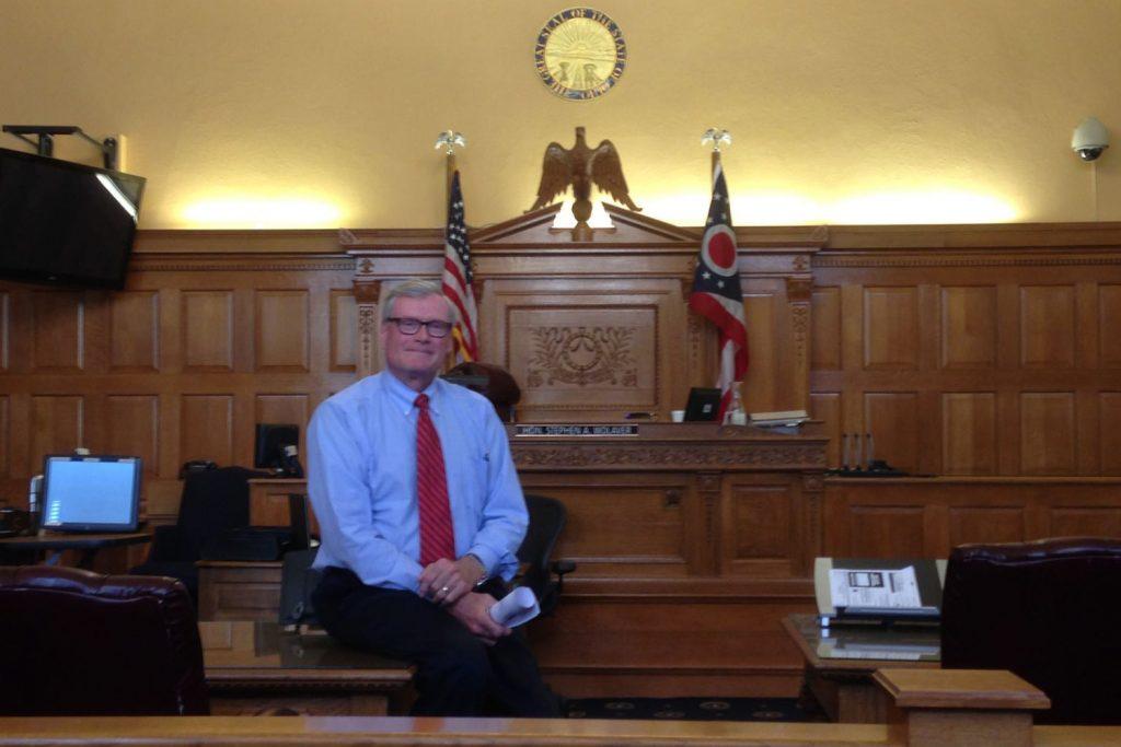 Ein Richter sitzt in seinem hellblauen Hemd und mit einer roten Krawatte vor seinem hölzernen Richterstuhl.