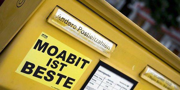 """Gelber Briefkasten auf welchem ein Kleber mit der Aufschrift """"Moabit ist Beste"""" klebt."""