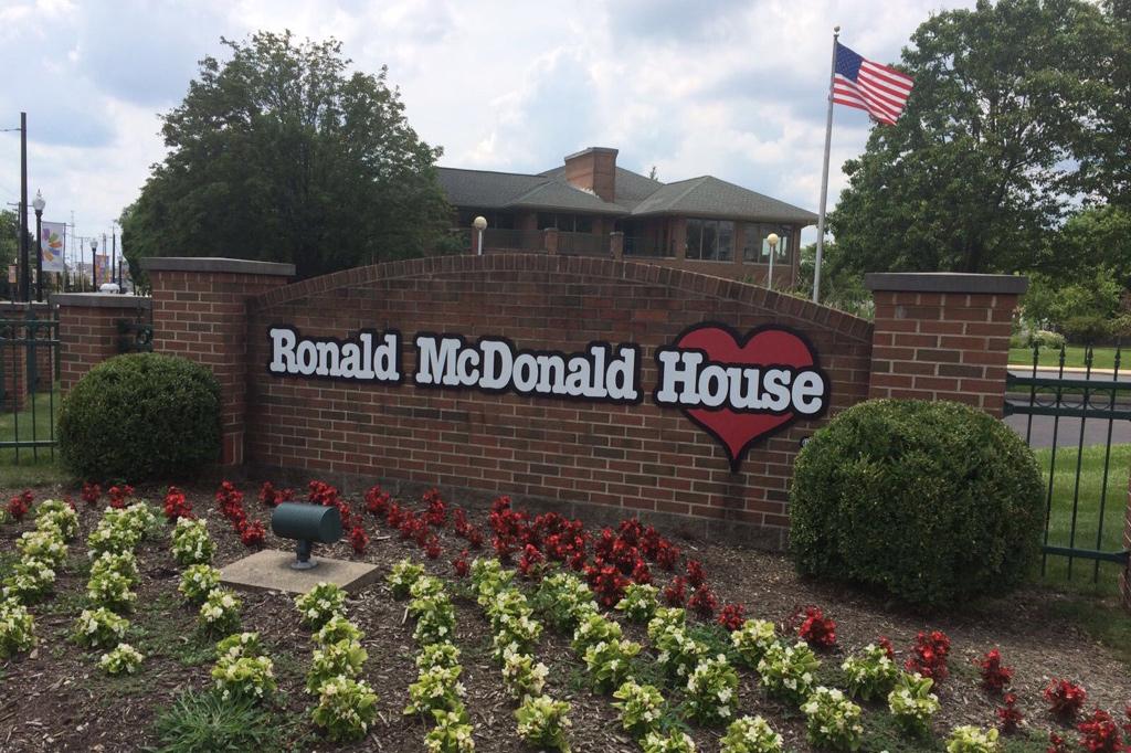 Ein kleiner Vorgarten mit gelb-grünen und roten Blümchen. Dahinter steht eine Mauer mit der Aufschrift «Ronald McDonald House» und im Hintergrund ist das Haus mit einer amerikanischen Flagge zu sehen.