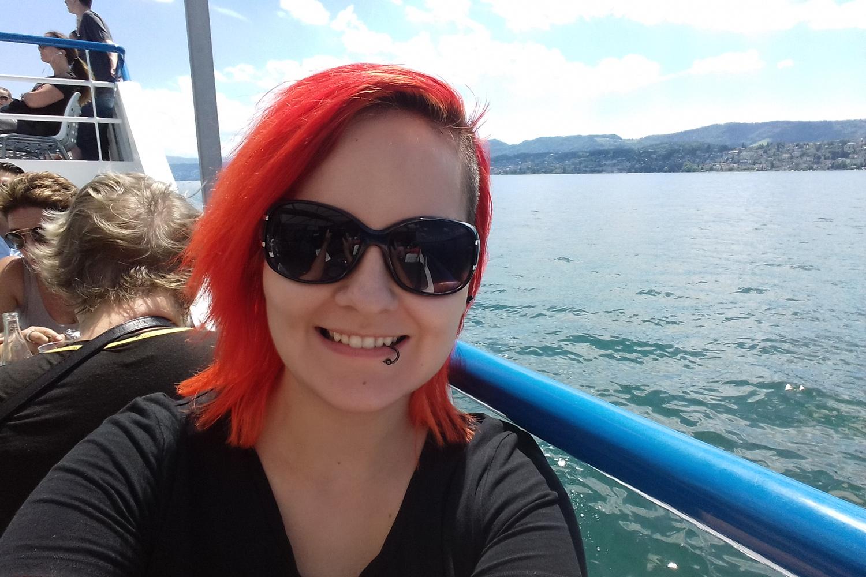 Rothaarige Austauschstudentin sitzt auf einem Schiff auf dem Zürichsee.