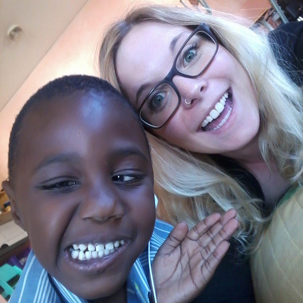 Selfie einer Austauschstudentin und einem namibischen Kind, die beide lächeln.