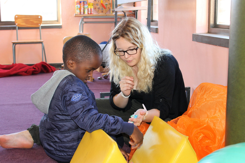 Austauschstudentin in einem Heim in Namibia mit einem Kind spielend am Boden.