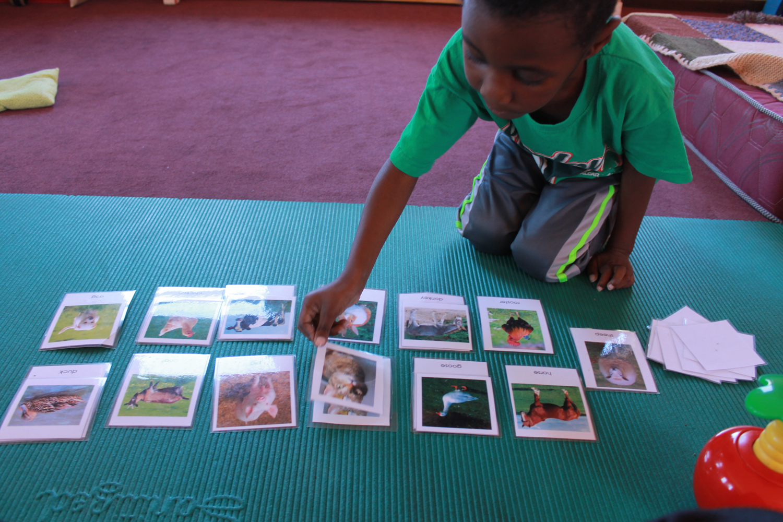 Ein Kind sitzt auf einer türkis farbenen Yoga-Matte und spielt Memory.