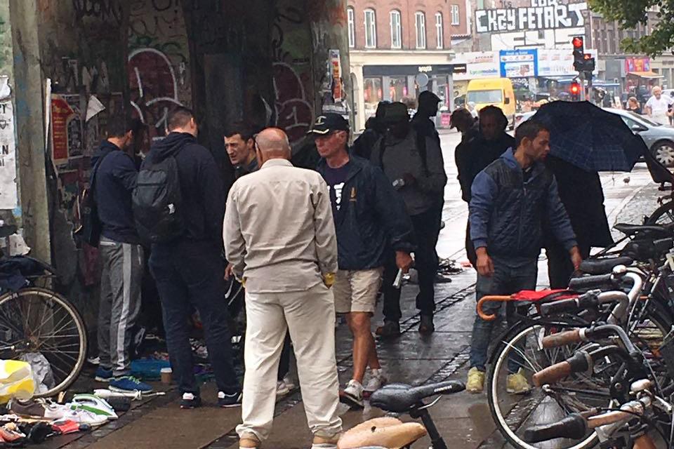 Obdachlose stehen unter einer Brücke. Daneben stehen Velos und es liegt viel Abfall herum.