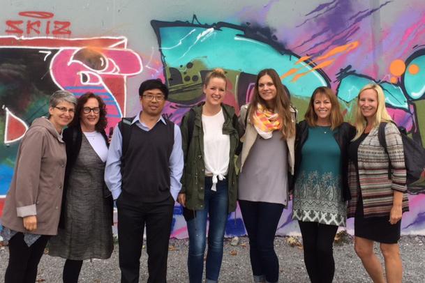Gruppenbild am Zürcher Letten vor einer Wand mit einem farbigen Graffiti.