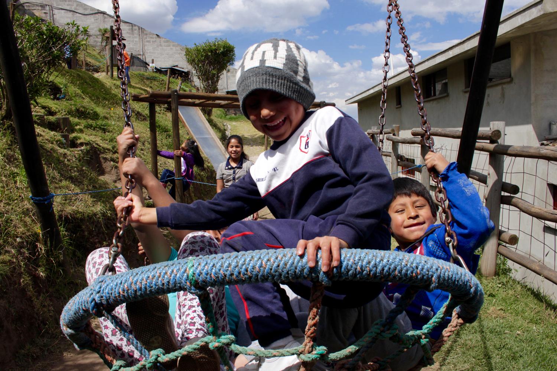 Kinder auf einer Schaukel auf einem Spielplatz in Ecuador.