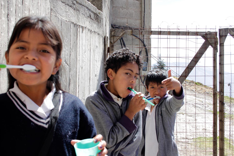 Zwei Buben und ein Mädchen stehen vor einem Zaun im Tagesheim in Quito, Ecuador und putzen sich draussen die Zähne.